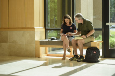Parents Ginger and John O'Neil of Midlothian, Virginia, consult registration info to plan their weekend after dropping off their daughter at Arrillaga Alumni Center