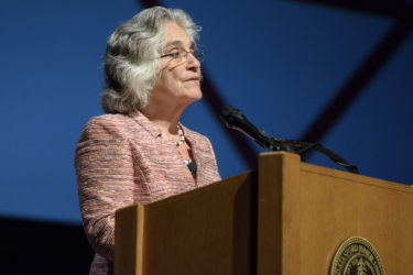 Persis Drell speaks from the lectern in Memorial Auditorium