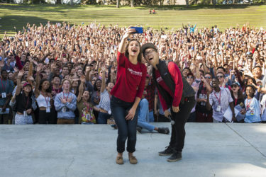 Seniors Cecilia Lang-Ree and Charlie Yang take a selfie with the entire class in the background.