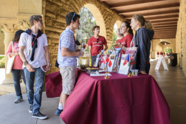 Students talk at an information table in the Main Quad