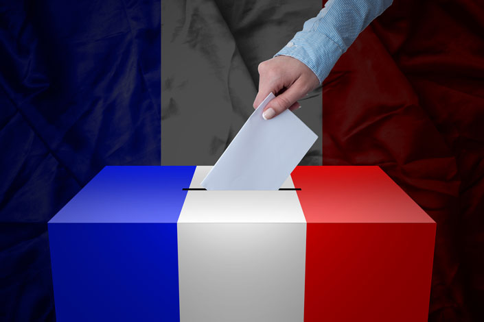 hand inserting a ballot into box decorated with French tricolor