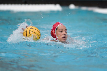 Maggie Steffens with the ball in a water polo match.