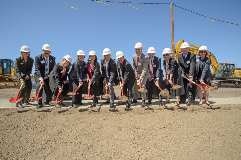 A group in hardhats holding shovels.