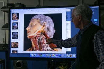 Paul Brown showing photograph of wax figures from collection dating between mid-17th and mid-19th centuries