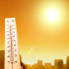 thermometer in foreground and city skyline in background under a blazing sun
