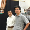Professor Shanhui Fan (left) and graduate student Sid Assawaworrarit standing by a device that wirelessly transmits energy to moving objects
