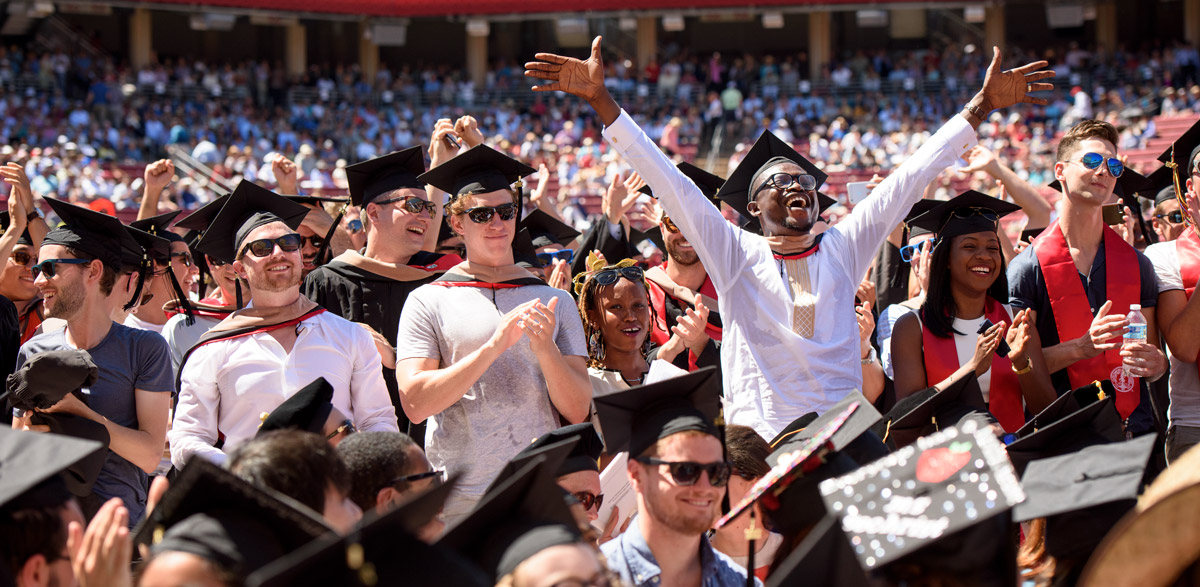 Students from the Graduate School of Business rise to receive their conferral of degrees.