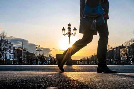 legs of a walker crossing th O'Connell Bridge in Dublin, Ireland