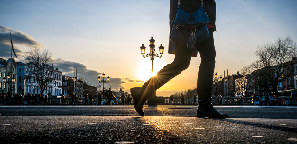 A pedestrian walks across O'Connell Bridge in Dublin, Ireland.