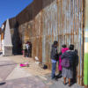 people at a gate at the Mexico-US border