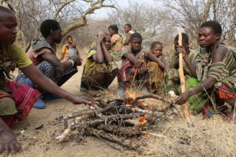 Members of the Hadza, a hunter-gatherer population in Tanzania, gathered around a fire.
