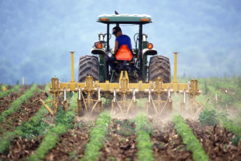 a farmer on a tractor tilling soil