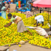 woman picking out oranges in street market in Accra, Ghana