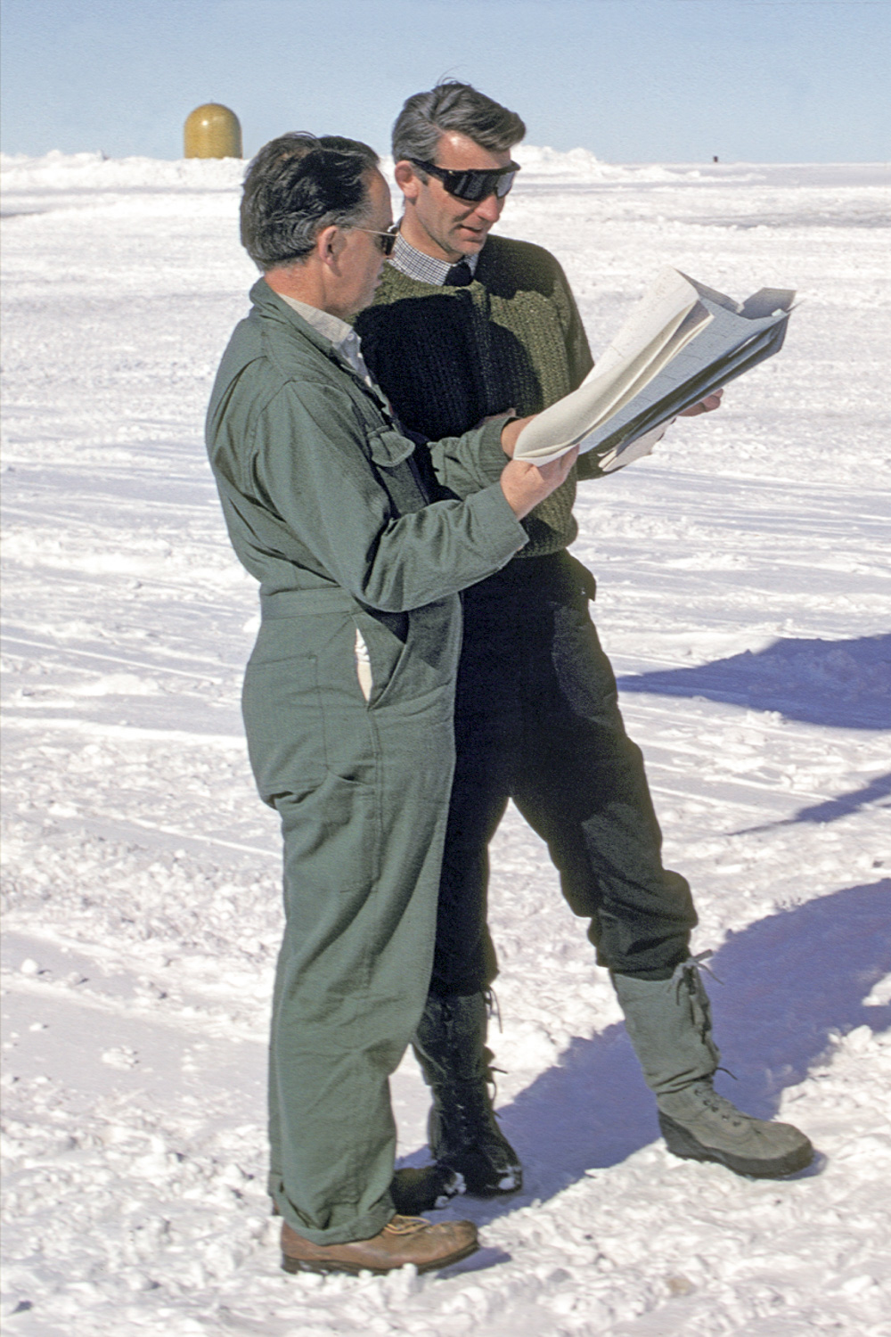 Gordon Robin (left) and Stan Evans discussing flights at Williams Field in Antarctica's McMurdo Sound in January 1970.