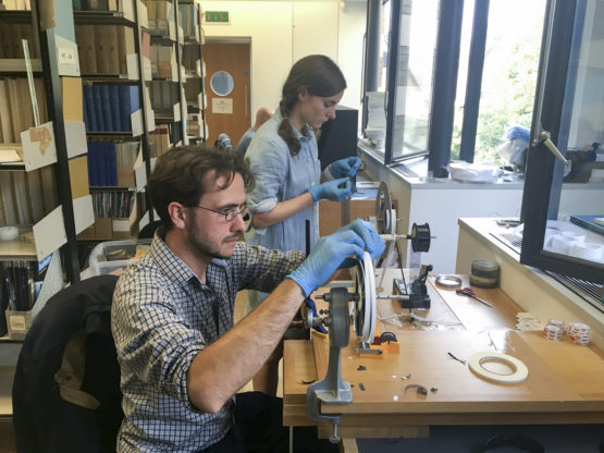 Professor Dustin Schroeder (foreground) and art historian Jessica Daniel splice 50-year-old film containing radar measurements of Antarctica into a reel in preparation for digital scanning at the Scott Polar Research Institute in the UK.