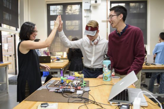 Professor Alison Okamura, left, celebrates a successful project with freshmen Brad Immel and Tiger Sun who worked on a team with Jonathan Sosa to create a Virtual Gear Shifter.
