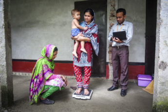 Study data collectors measure a child's growth in Dhaka, Bangladesh, to assess impact of water, sanitation and hygiene interventions.