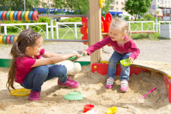kids squabbling over a toy in a playground sandbox