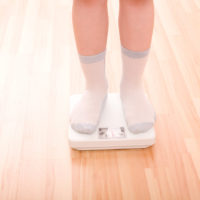 Overweight child standing on scales.
