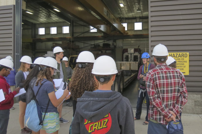 Students in hard hats stand outside a warehouse)