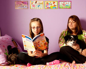 Janet Cartwright sits on a bed with a dog while her daughter reads