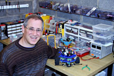 Steven Paley sitting at a work bench covered in engineering parts