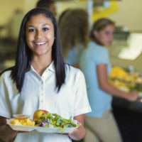 High school student holds a plate of healthy food in the school cafeteria. Her classmates are waiting in line in the background.
