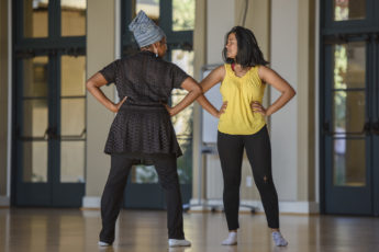 Dance lecturer Aleta Hayes, left, coaches a student in her presentation.