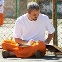 Man reading books at prison yard