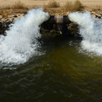Water gushes from a pipe into a farm irrigation canal in Central California.