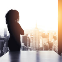 Silhouette of woman standing alone in boardroom