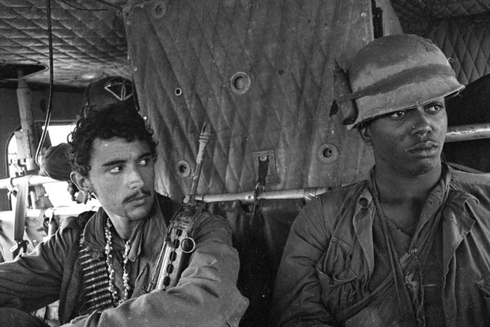Private First Class Danny Pratti, 21 (left), and Private First Class Freddie Bradshaw, 20, both from A Company, 4th Battalion, 31st Infantry Regiment, 196th Light Infantry Brigade, are picked up by a chopper in the field. March 1968, Quế Sơn)