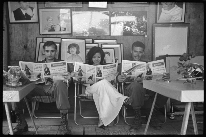 Two soldiers and a young woman reading Overseas Weekly)