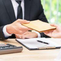 corruption concept -- businessman and woman exchange a brown envelope