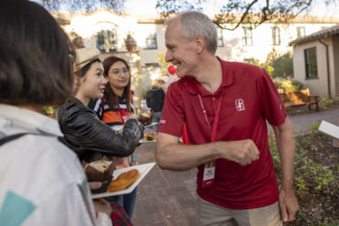 Stanford President Marc Tessier-Lavigne bumps elbows with frosh whose hands are full.