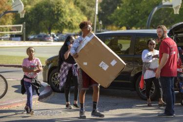 Freshman Yosheb Getachew of Parker, Colorado, carries some of his belongings to his dorm.