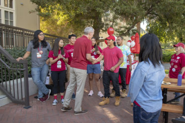 Pilli Cruz-DeJesus is greeted by Stanford President Marc Tessier-Lavigne and the staff of Muwekma-Tah-Ruk, the Native American theme house.