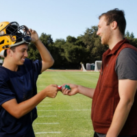 A man hands a football player a mouthguard.