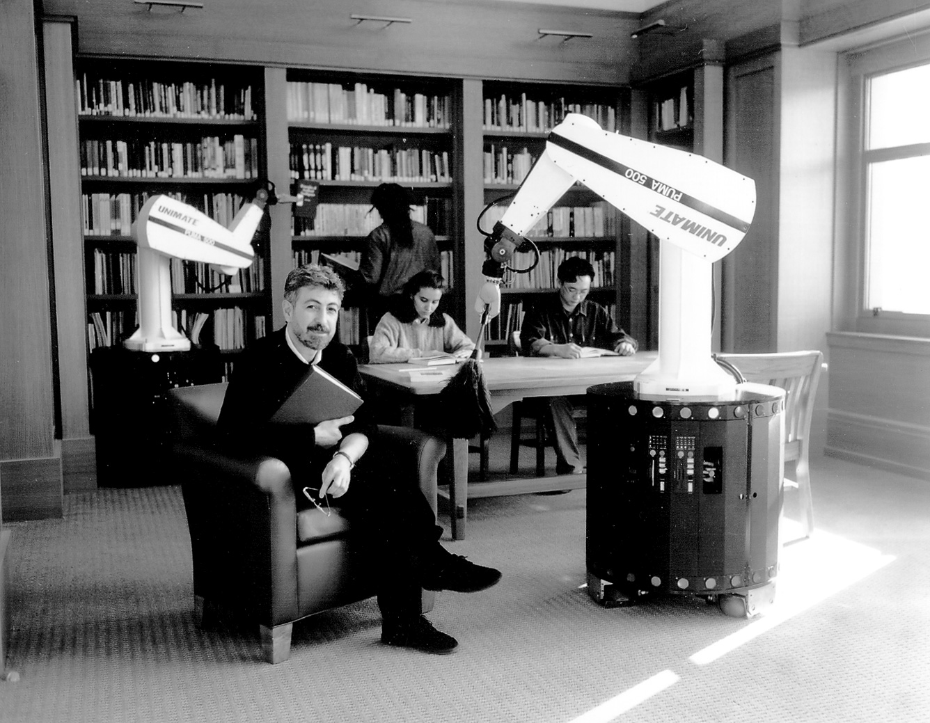 Khatib sitting in a library with two robot arms