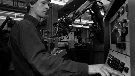 Cutkosky at a machine with a robotic arm next to him