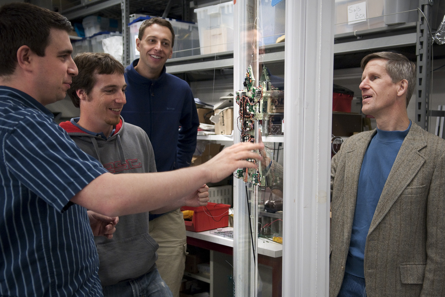 Four men watch Stickybot climb up a pane of glass