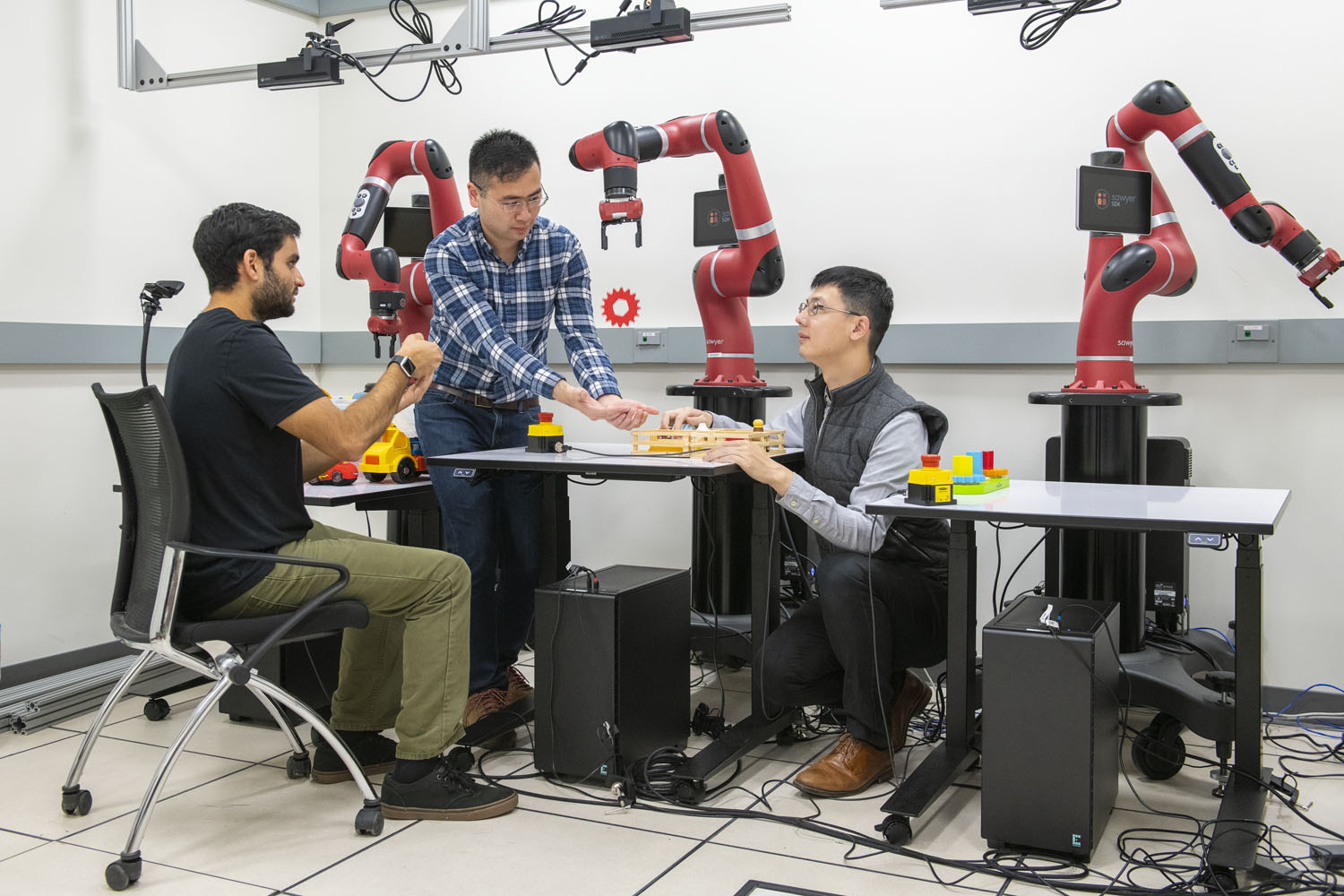 Using a handheld device, Ajay Mandelkar, Jim Fan and Yuke Zhu use their software to control the robot arm.
