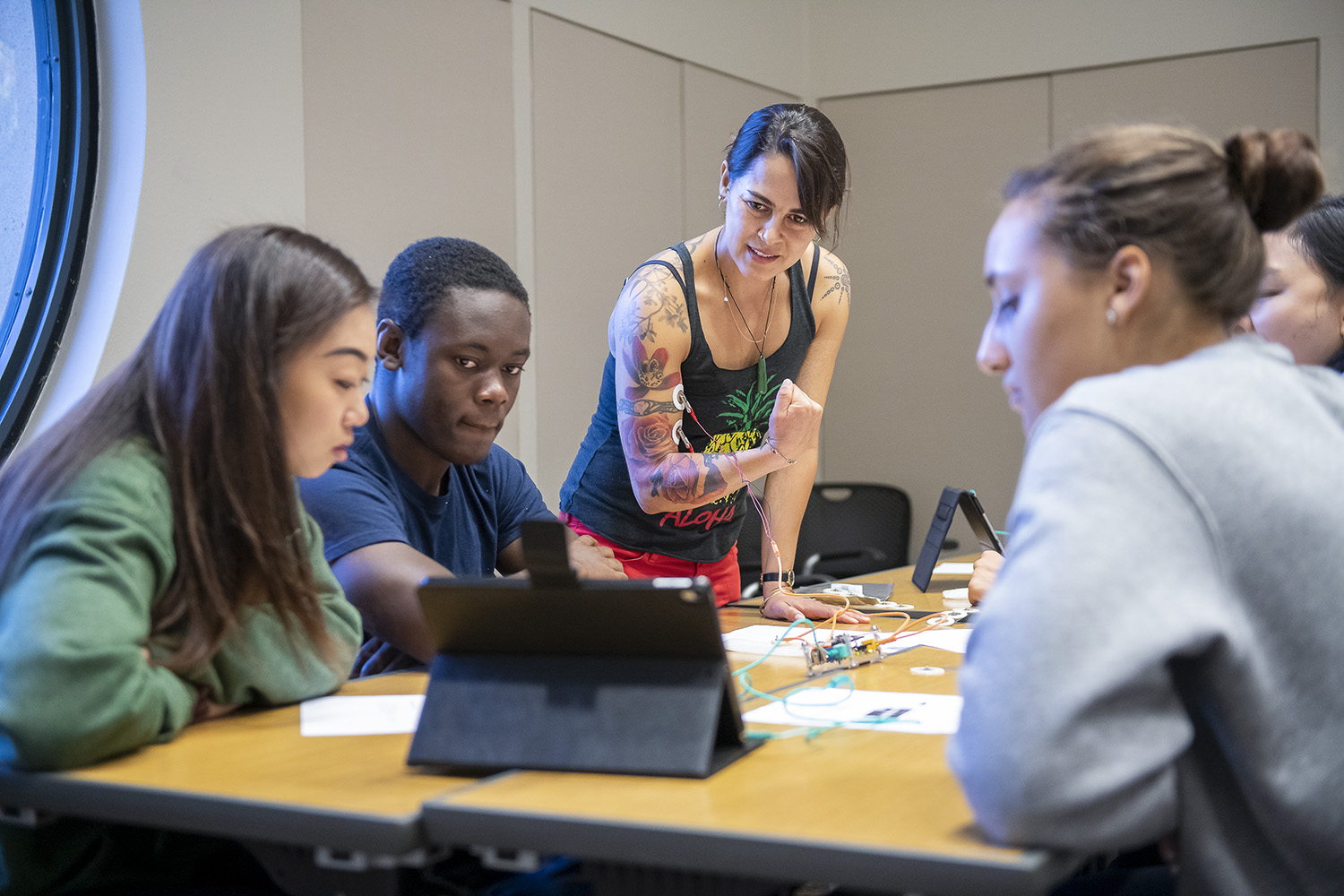 "Stanford lecturer Lupita Ruiz-Jones (center) generates electrical impulses on an iPad by flexing her bicep muscles – electrodes attached – during a class meeting of ""How Does Your Brain Work"" with undergraduate students Kelsey Wang and Layo Laniyan (left) and Sophie Dixon (right). Ruiz-Jones, who earned a PhD in marine biology at Stanford, is also an alumna of its Diversifying Academia, Recruiting Excellence Doctoral Fellowship Program."