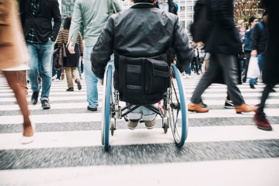 Wheelchair user from behind in a busy pedestrian zone
