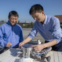 Professor Shanhui Fan and postdoctoral scholar Wei Li atop the Packard Electrical Engineering building with the apparatus that is proving the efficacy of a double-layered solar panel. The top layer uses the standard semiconductor materials that go into energy-harvesting solar cells, the novel materials on the bottom layer perform the cooling task.
