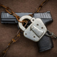 Pistol behind lock and chains symbolic of gun control