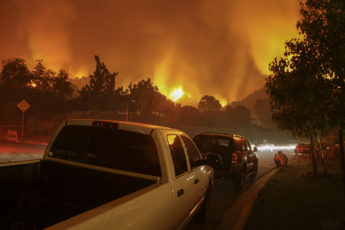 Residents of a neighborhood sit by and watch a fire threaten their homes.