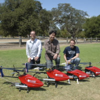 Three men kneeling behind three radio-controlled helicopters outside