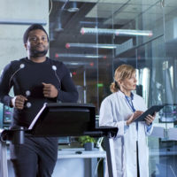 Male Athlete Walks on a Treadmill with Electrodes Attached to His Body while Sport Scientist Interacts with Touchscreen and Supervises EKG Status. In the Background Laboratory with High-Tech Equipment.