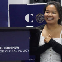 Student Yvonne Lee standing near a banner with logo of Carnegie-Tsinghua logo